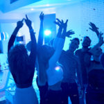 Group of modern young people dancing under confetti at private house party lit by blue light